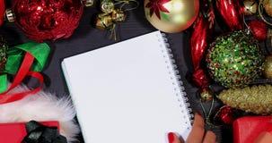 Hand puts empty notepad between Xmas ornaments stock footage