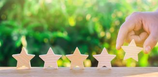 Hand puts the fifth wooden star. Get the fifth star. The concept of the rating of hotels and restaurants, the evaluation of critic. S and visitors. Quality level stock image