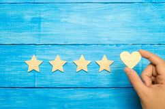The hand puts the heart to the four stars. Choice of buyers. Universal recognition and admiration. Rating of a hotel or restaurant royalty free stock image