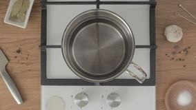 Hand puts metal pan with water on gas stove and takes it off on bright kitchen