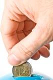 An hand puts a money into a moneybox. An hand puts a money into a blue moneybox Royalty Free Stock Image