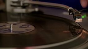 Hand puts needle on spinning vinyl record player. Turntable starts spinning and audio needle is set by hand on vinyl record to play stock footage