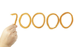 Hand puts the number of ten thousand of bagels Royalty Free Stock Image