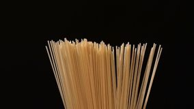 Hand puts pasta in the pan, on black, rotation stock video