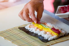 Hand puts piece of fish. Stock Photography