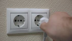 Hand puts a power plug in the dirty, unclean wall socket.  stock footage