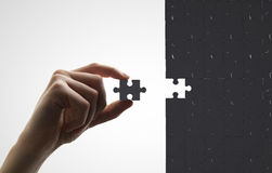 Hand puts puzzle Royalty Free Stock Photos