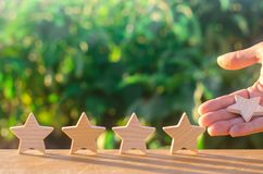 Hand puts / removes the fifth wooden star. Get the fifth star. The concept of the rating of hotels and restaurants, the evaluation. Of critics and visitors stock photography