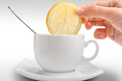 Hand puts a slice of lemon in cup of tea. Women hand putting a slice of lemon in cup of tea Royalty Free Stock Photo