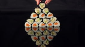 Hand puts sushi on a pyramid on black background. stock video footage