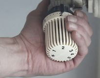 White heating thermostat. Hand puts the temperature in a white heating thermostat Royalty Free Stock Photography
