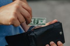 Hand puts toy banknote into wallet. Toy money. A hand is hiding a miniature dollar bill in a black purse royalty free stock photo