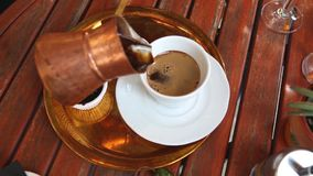 Hand puts the traditional hot greek coffee in the glass stock footage