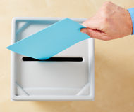 Hand putting ballot in ballot box Stock Images