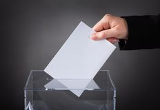Hand putting ballot in box Stock Photos