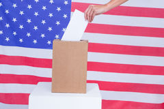 Hand putting ballot in vote box behind american flag Royalty Free Stock Images