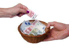 Hand putting a banknote in a basket Royalty Free Stock Photo
