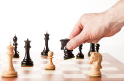 Hand putting a black chess piece on a table Stock Photo