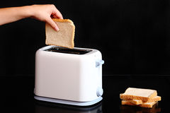 Hand putting bread to toaster Stock Photos