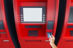 Hand putting card in ATM machine. Close up of hand inserting credit card into red ATM machine with empty white screen. Monetary operation concept. Mock up, 3D Royalty Free Stock Photo