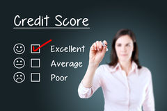 Hand putting check mark with red marker on excellent credit score evaluation form. Blue background. Stock Image