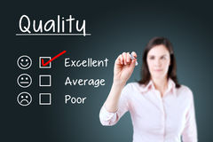 Hand putting check mark with red marker on excellent quality evaluation form. Blue background. Stock Image