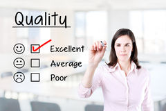 Hand putting check mark with red marker on excellent quality evaluation form. Office background. Royalty Free Stock Images