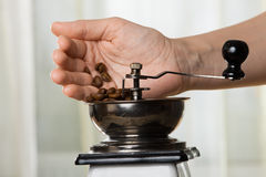 Hand putting coffee beans to grinder, closeup Stock Photos