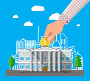 Hand putting coin into bank building Royalty Free Stock Photos