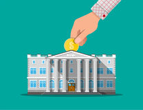 Hand putting coin into bank building Royalty Free Stock Photo