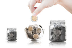 Hand putting coin into glass container,coins in a glass jar against Stock Image