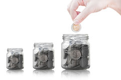 Hand putting coin into glass container,coins in a glass jar against Royalty Free Stock Photo