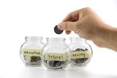 Hand putting coin in glass container with travel, saving and education labels Royalty Free Stock Images