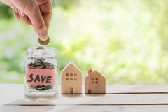 Hand putting coin in glass jar of coin for saving money for buying house. Real estate concept Stock Photos