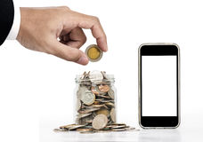 Hand putting coin and glass jar full of coins with mobile phone, isolated screen for copy space Royalty Free Stock Photography