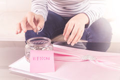 Hand putting a coin into glass jars with 'wedding' text Stock Photo