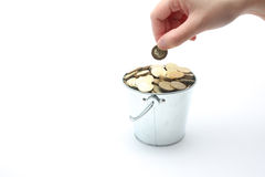 Hand putting coin in money filled tin bucket - Series 4 Royalty Free Stock Image