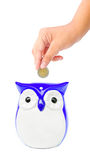 Hand putting coin into a owl bank Royalty Free Stock Images