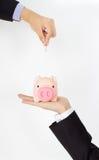 Hand putting coin into a piggy bank. Men hand putting coin into a piggy bank Stock Photo