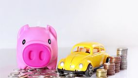 Hand putting a coin into the piggy bank with a car of toy and co. Ins stacked on white background. Saving money concept, with copy space for your text stock video
