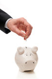 Hand putting coin in piggy Bank Stock Images