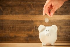 Hand Putting a Coin in Piggy Bank. Money box pig coin put moneybox table Royalty Free Stock Images