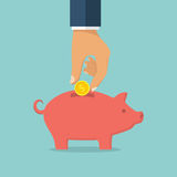 Hand putting coin into piggy bank Stock Photography