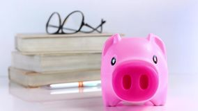 Hand putting a coin into the piggy bank on white background. Saving money concept, focus on the piggy bank. with copy space for your text stock footage