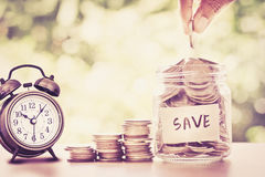 Hand putting Coins in glass jar , time for money saving financi stock images