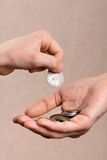Hand putting coins in the hand of another person Stock Images