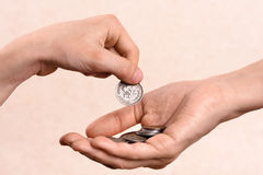 Hand putting coins in the palm of another person Stock Photography