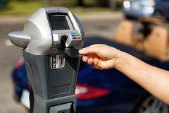 Hand putting credit card into parking meter with convertible car Stock Photography