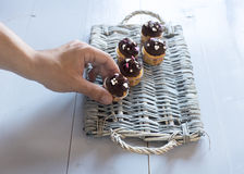 Hand putting a delicious chocolate cupcakes on a wicker tray Royalty Free Stock Photos