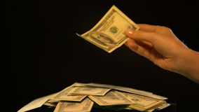Hand putting dollar to cash pile isolated on black, financing and crowdfunding. Stock footage stock video footage